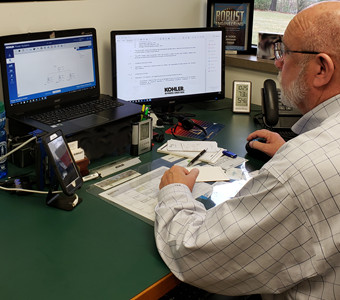 Kinsley Group employee at desk in office using KOHLER generator sizing tool on computer